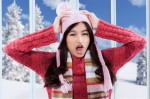 Confused girl with winter clothes at home