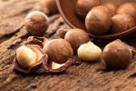 Close up the macadamia nuts on wooden plate